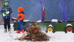 I bambini felici del villaggio in vestiti luminosi e caldi bighellonano il fuoco di accampamento dai rami contro grigio recintano video d archivio