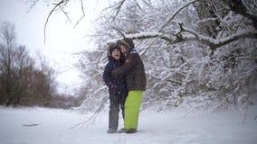 I bambini felici e divertenti che stanno sotto l'albero da cui la neve cade Due tipi che sorridono e genuino felici E archivi video