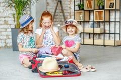 I bambini felici imballano le cose in una valigia su un viaggio Concetto t Fotografie Stock