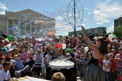 I bambini felici prendono le bolle di sapone sulla via nella città di T Fotografie Stock