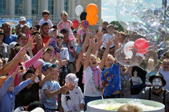 I bambini felici prendono le bolle di sapone sulla via nella città di T Fotografie Stock Libere da Diritti