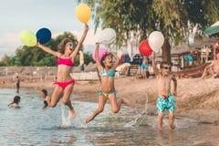 I bambini felici saltano e divertendosi con i palloni nell'acqua fotografia stock