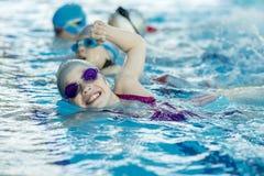 I bambini felici scherza il gruppo alla classe della piscina che impara nuotare Fotografie Stock