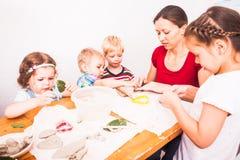 I bambini felici sono impegnati con argilla da modellare fotografie stock