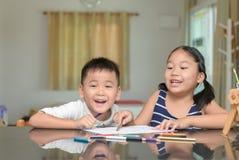 I bambini felici stanno dipingendo le immagini con le matite variopinte fotografia stock libera da diritti