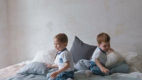 I bambini gemellati dei ragazzi stanno trovando sul letto, cuscini di lancio, saltare e ridere archivi video