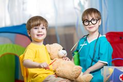 I bambini giocano al dottore con il giocattolo della peluche Fotografia Stock