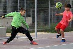 I bambini giocano a calcio nel cortile della scuola fotografie stock