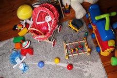 I bambini giocano la stanza con i giocattoli sul pavimento Immagini Stock