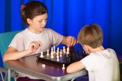 I bambini giocano un gioco da tavolo chiamato scacchi immagine stock libera da diritti
