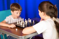 I bambini giocano un gioco da tavolo chiamato scacchi fotografie stock