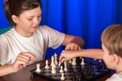 I bambini giocano un gioco da tavolo chiamato scacchi immagini stock
