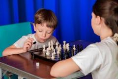 I bambini giocano un gioco da tavolo chiamato scacchi fotografia stock libera da diritti
