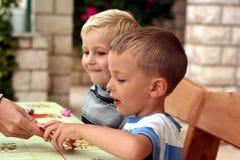 I bambini giocano un gioco di tabella Fotografie Stock Libere da Diritti