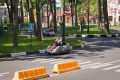 I bambini guidano sul kart nel parco Immagine Stock