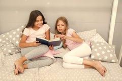 I bambini hanno letto il libro in base Tradizione della famiglia I migliori amici delle ragazze hanno letto la fiaba prima di son immagine stock