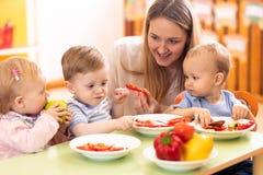 I bambini hanno un pranzo nel centro di guardia Bambini che mangiano alimento sano nell'asilo Insegnante della scuola materna con fotografie stock
