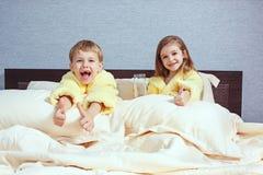 I bambini, il ragazzo e la ragazza di risata felici in accappatoio molle dopo il bagno giocano sul letto bianco Fotografia Stock