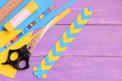 I bambini incartano il segnalibro su un fondo di legno lilla con lo spazio della copia per testo Mestieri di carta facili a casa  Fotografia Stock