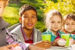 I bambini internazionali si siedono con le tazze fuori Immagini Stock