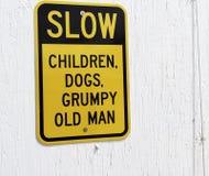 I bambini lenti, i cani e l'uomo anziano scontroso firmano Immagini Stock