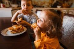 I bambini mangiano i pancake dolci per la prima colazione Fotografia Stock Libera da Diritti