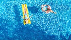 I bambini nel fom aereo di vista del fuco della piscina qui sopra, bambini felici nuotano sulla ciambella gonfiabile dell'anello  immagine stock libera da diritti
