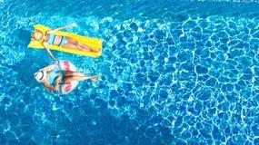 I bambini nel fom aereo di vista del fuco della piscina qui sopra, bambini felici nuotano sulla ciambella gonfiabile dell'anello  fotografia stock libera da diritti