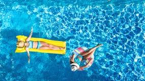 I bambini nel fom aereo di vista del fuco della piscina qui sopra, bambini felici nuotano sulla ciambella gonfiabile dell'anello  fotografia stock