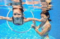 I bambini nuotano in stagno subacqueo, ragazze attive felici si divertono sotto l'acqua Fotografie Stock