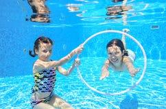 I bambini nuotano in stagno subacqueo, ragazze attive felici si divertono sotto l'acqua Fotografia Stock Libera da Diritti