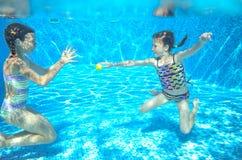 I bambini nuotano in stagno subacqueo, ragazze attive felici si divertono sotto l'acqua Immagini Stock Libere da Diritti