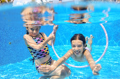 I bambini nuotano in stagno subacqueo, ragazze attive felici si divertono sotto l'acqua, sport dei bambini Immagine Stock