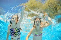 I bambini nuotano in stagno underwater, ragazze si divertono in acqua Fotografia Stock