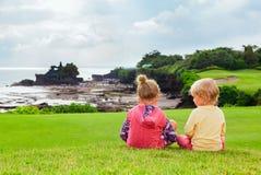 I bambini osservano dall'alta scogliera il lotto di Tanah del tempio di balinese Fotografie Stock