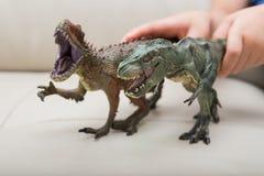 I bambini passa la cattura un Carcharodontosaurus marrone e del giocattolo verde di tirannosauro Fotografia Stock Libera da Diritti