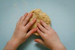 I bambini passano con la taglierina dei biscotti sulla pasta dei biscotti Fotografie Stock Libere da Diritti