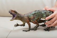 I bambini passano la cattura un Carcharodontosaurus marrone e del giocattolo verde di tirannosauro Fotografia Stock Libera da Diritti