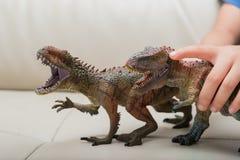 I bambini passano la cattura un Carcharodontosaurus marrone e del giocattolo verde di tirannosauro Immagini Stock