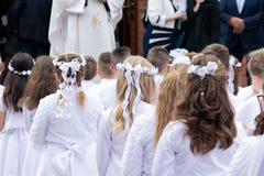 I bambini per la prima comunione stanno aspettando davanti alla chiesa fotografia stock