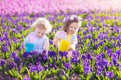 I bambini piantano ed innaffiano i fiori nel giardino di primavera Fotografie Stock Libere da Diritti