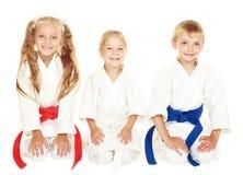 I bambini piccoli allegri da sedersi in un karatè cerimoniale del kimono posano Fotografie Stock Libere da Diritti