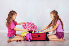 I bambini raccolgono l'abbigliamento in valigia Fotografia Stock