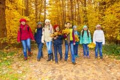 I bambini raggruppano con le foglie di acero che i mazzi camminano insieme Fotografia Stock