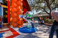 I bambini restano alla scultura dell'astronauta vicino al negozio del giocattolo Immagini Stock Libere da Diritti