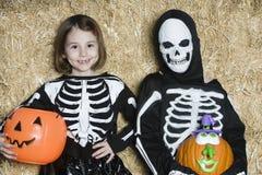 I bambini in scheletro Costumes le Jack-O-lanterne della tenuta Fotografia Stock Libera da Diritti