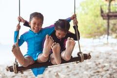 I bambini scoprono i piedi con la sabbia mentre essi che giocano insieme sull'le oscillazioni alla spiaggia vicino al mare nella  fotografie stock libere da diritti
