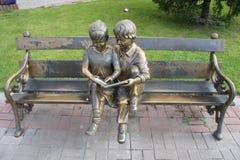 I bambini scultorei della composizione che leggono un libro in uno dei cortili nel centro di Irkutsk Fotografie Stock