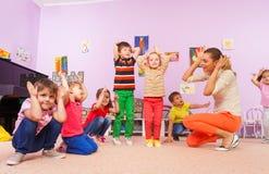 I bambini si ripetono dopo l'insegnante che fa le orecchie con le mani fotografie stock