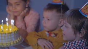 i bambini si siedono alla tavola rossa con il dolce e soffiano nei ventilatori multicolori del partito alla festa di compleanno archivi video
